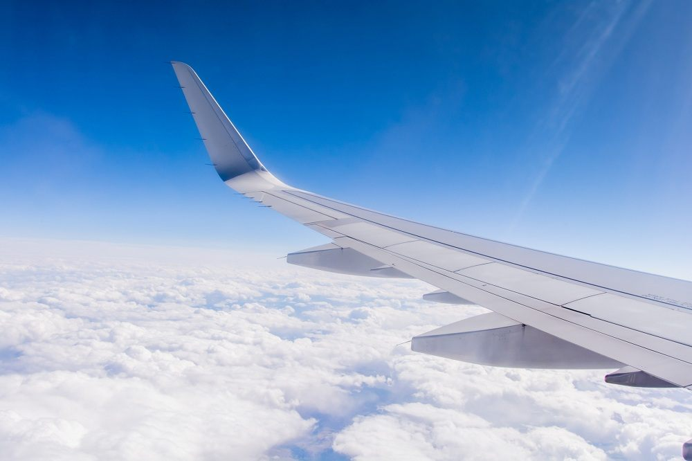 Airplane wing in sky & clouds