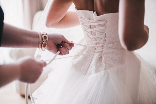 A bride being dressed in a gown.