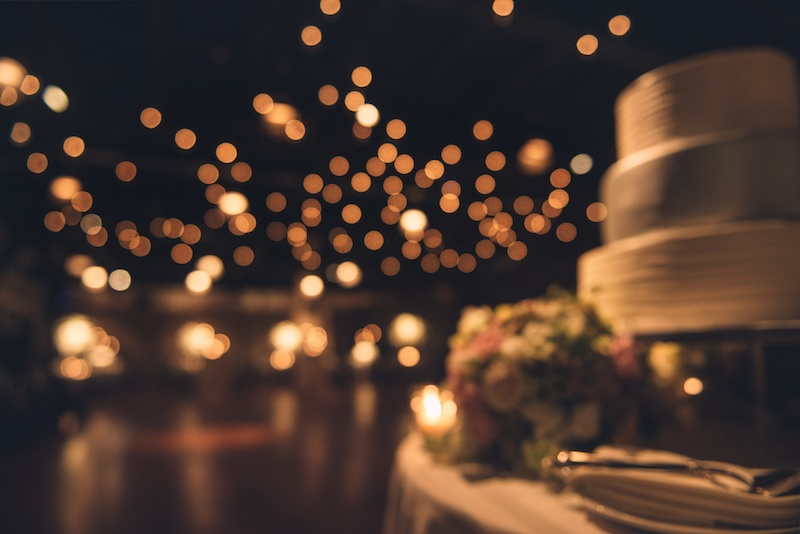 Wedding party evening. Blurred dance floor and wedding cake. Wedding invitation background