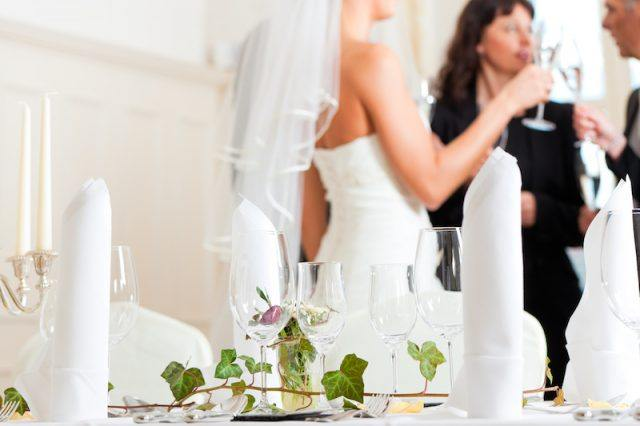 A bride speaking with guests at a wedding.