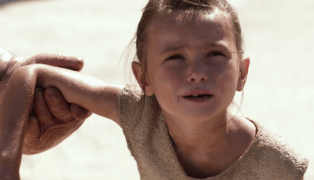 Young Rey's arm being held as she looks upward.