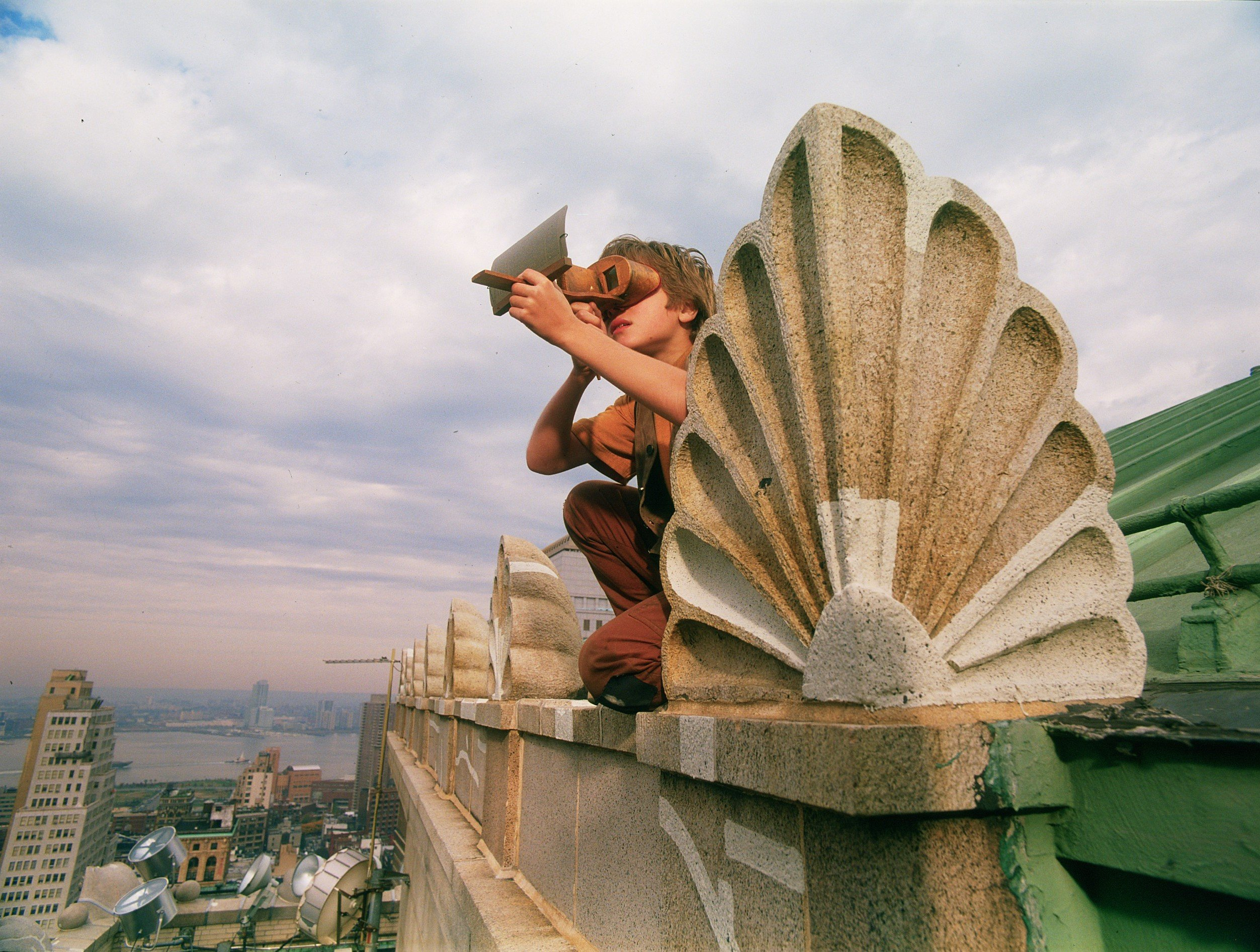 A boy looking through a 3D apparatus on a roof in front of the New York City skyline.