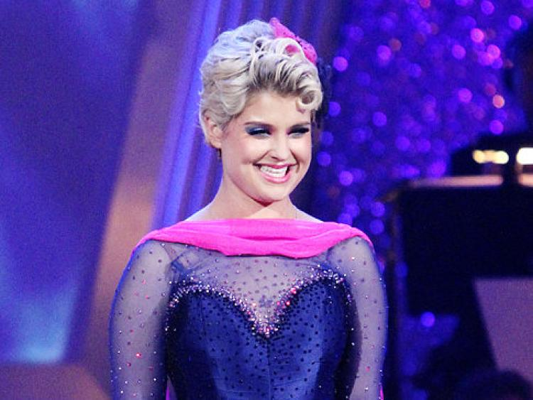 Kelly Osbourne stands in a blue outfit on Dancing With the Stars