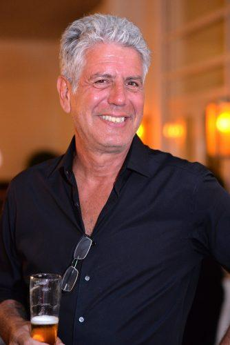 Anthony Bourdain drinking from a glass at an event.