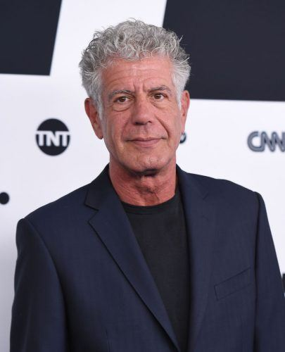 Anthony Bourdain wearing a blue blazer on a red carpet.