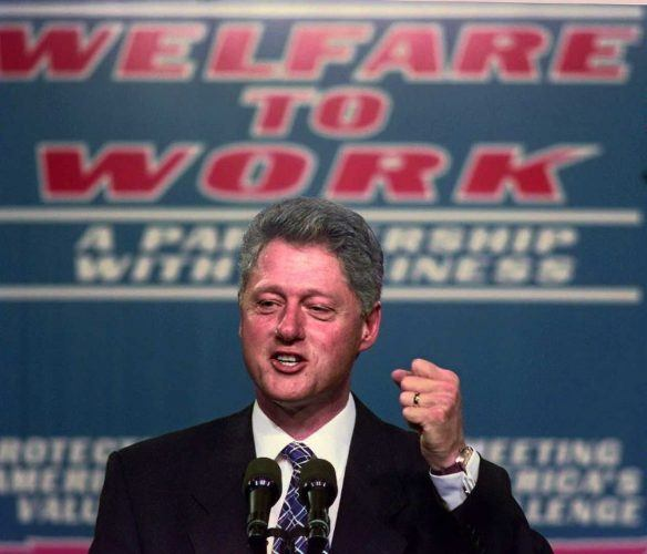 Bill Clinton stands in front of a podium.