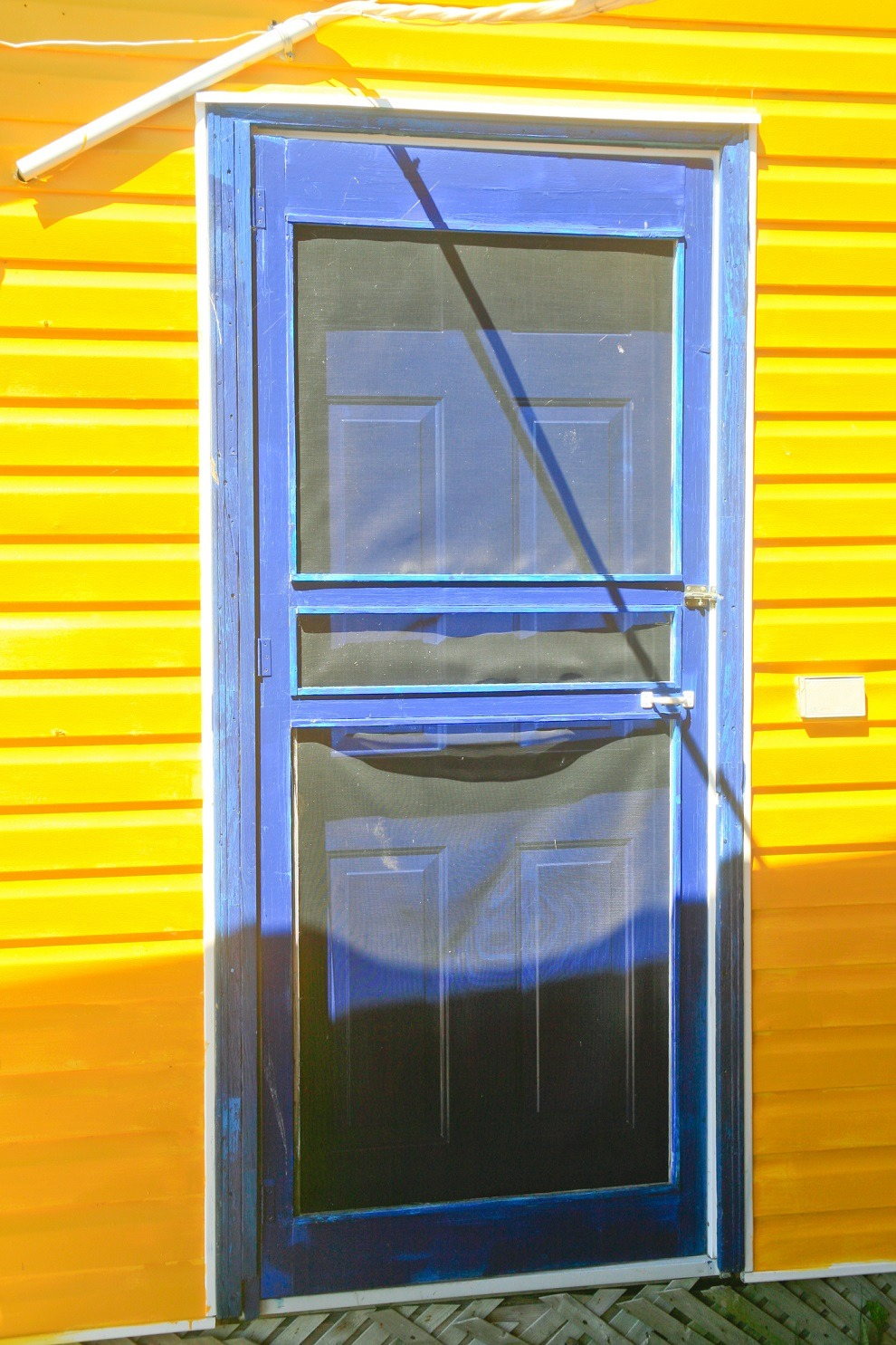 Blue screen door and yellow house