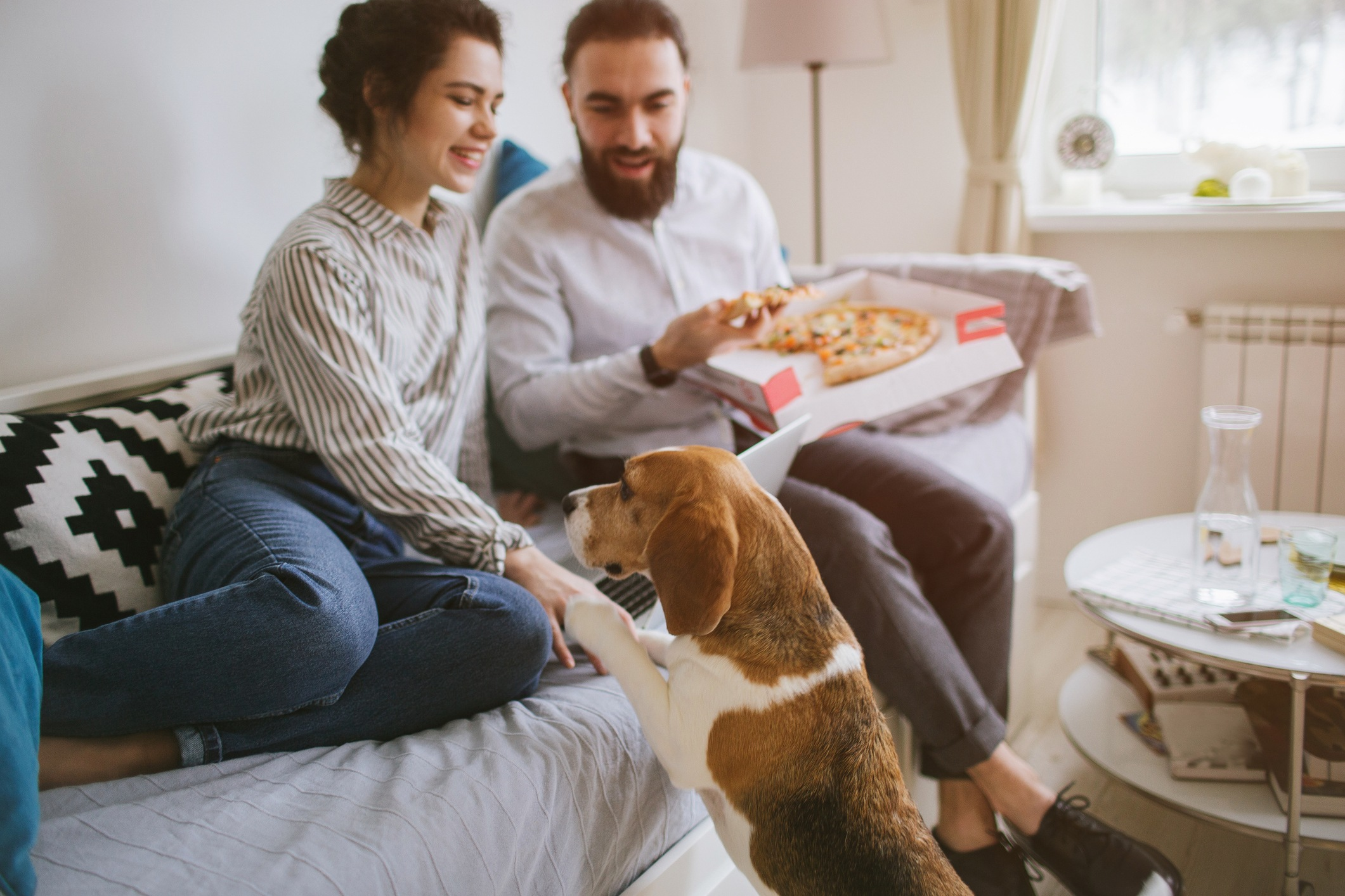 Couple with dog and pizza