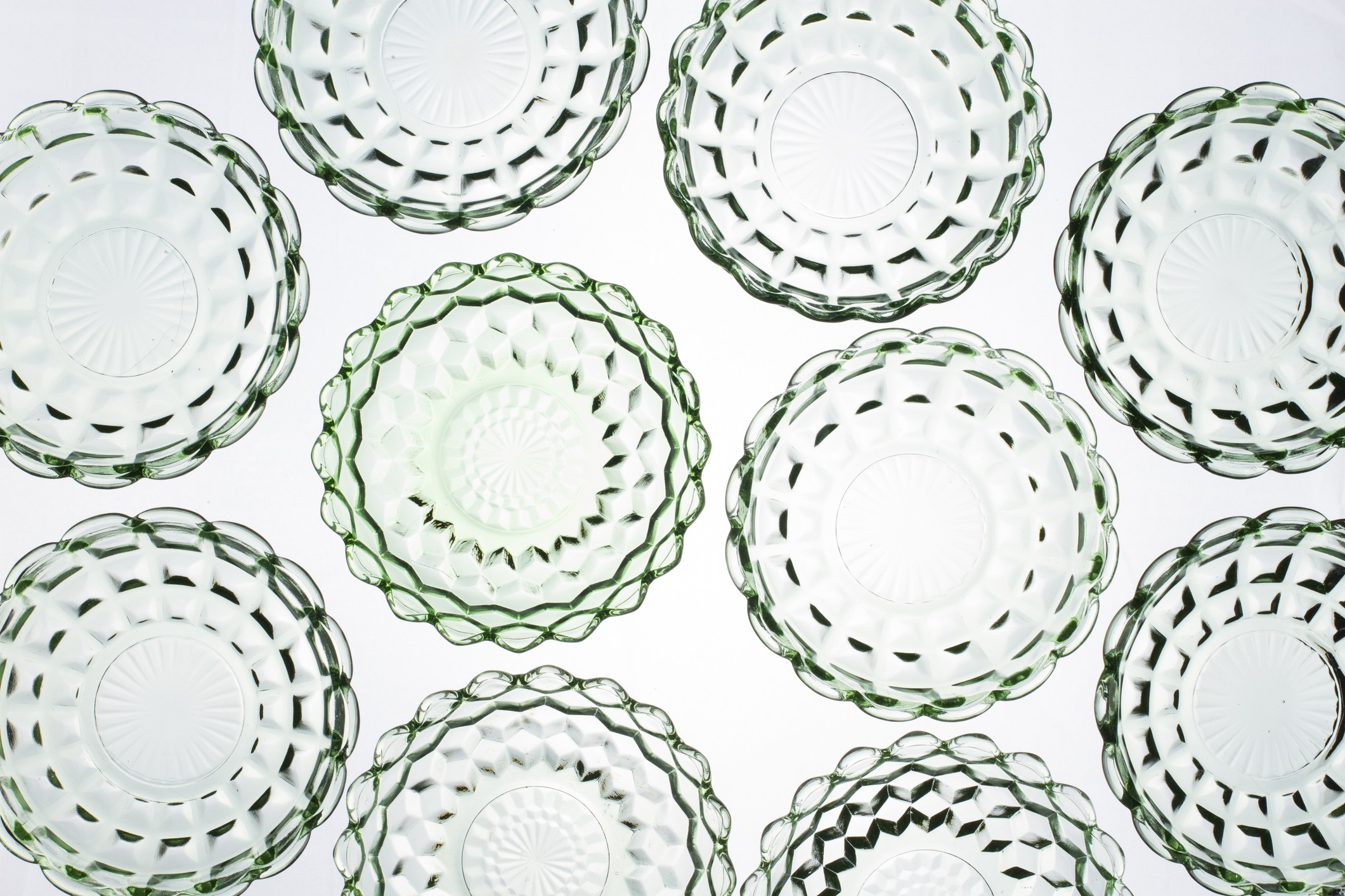 Green Depression glass bowls, back lit, shot from above to form an abstract pattern.