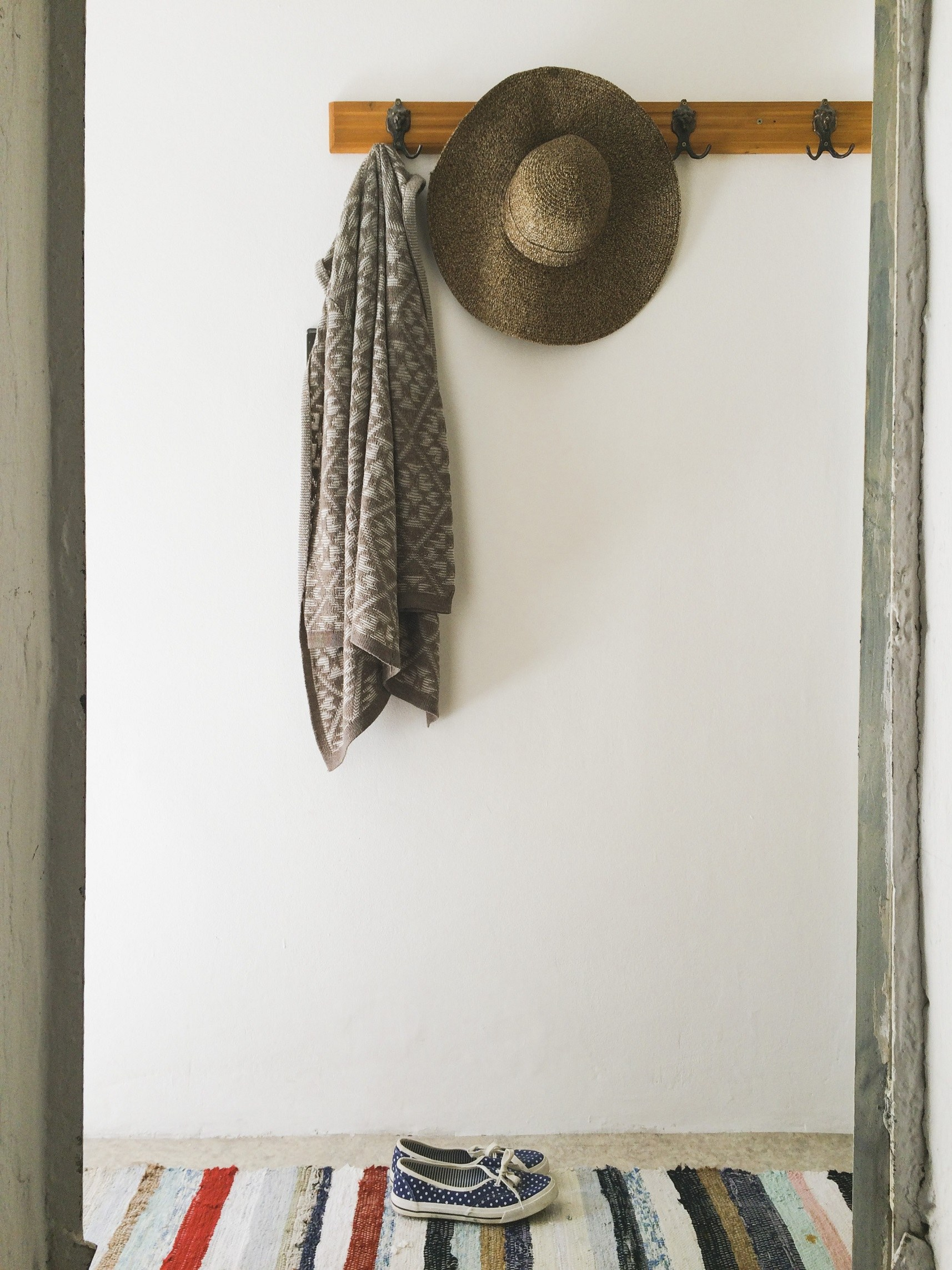 A coat and a hay cap hanging on the wall. Espadrilles underneath. Colorful rug.