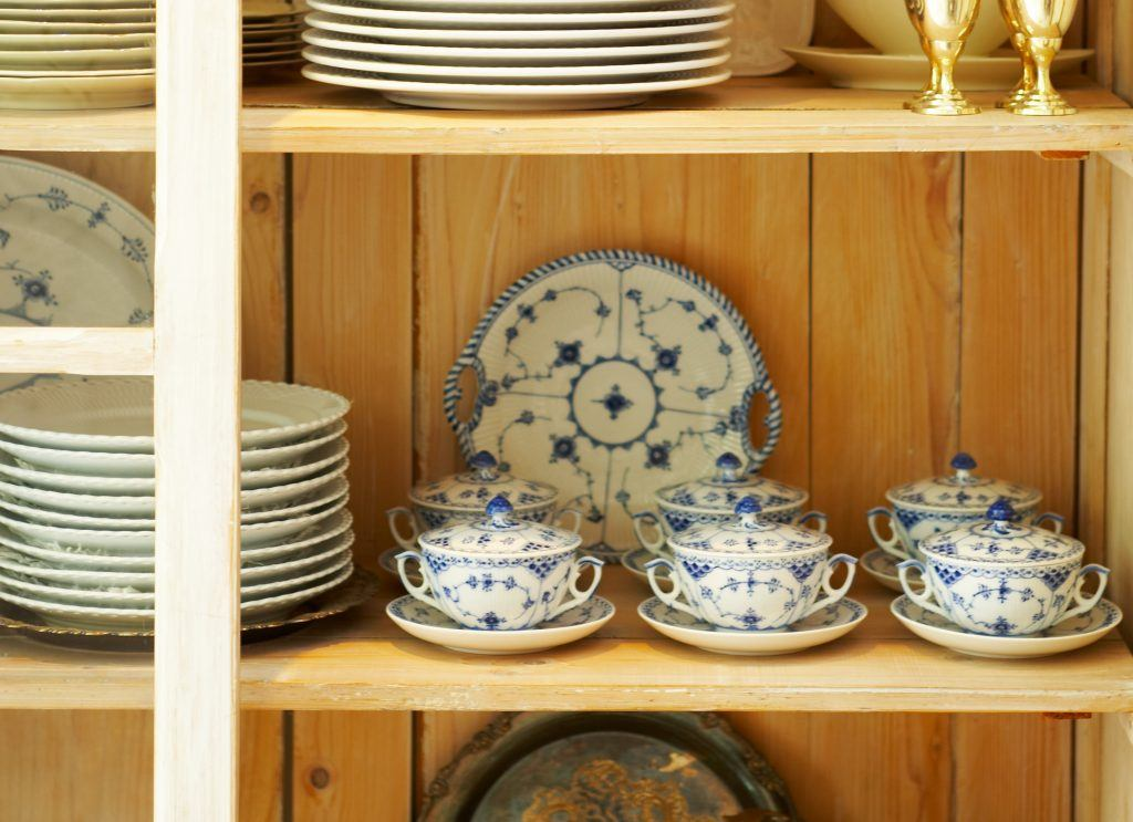 A close-up picture of a beautiful old cupboard, filled with plates, glasses and dishes.
