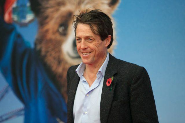 Hugh Grant poses at a movie premiere.