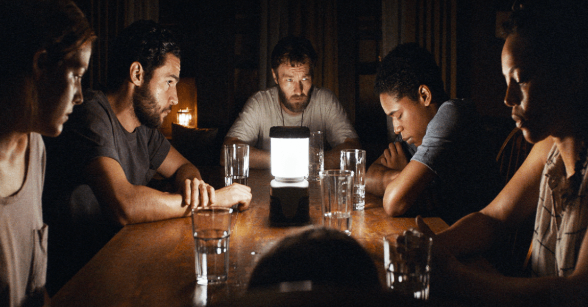 A group of people sitting around a table in the dark