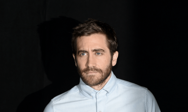 Jake Gyllenhaal stands in front of a dark background.