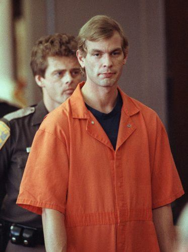 Jeffrey Dahmer in a prison uniform being followed by a policeman.