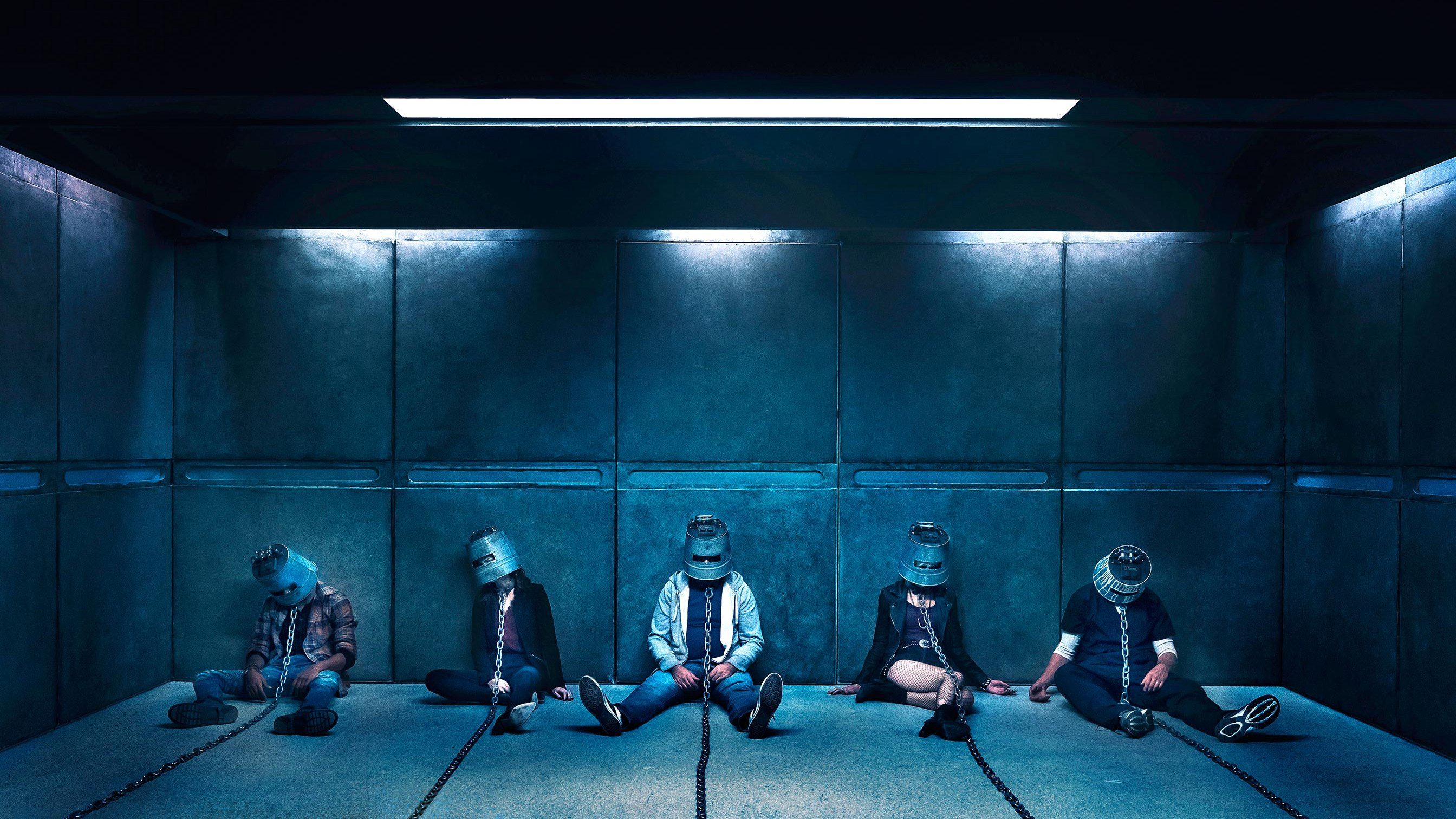 Five people wearing helmets and chains sit in a cell.
