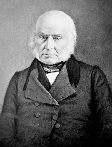 John Quincy Adams sitting down on a chair and staring straight ahead.