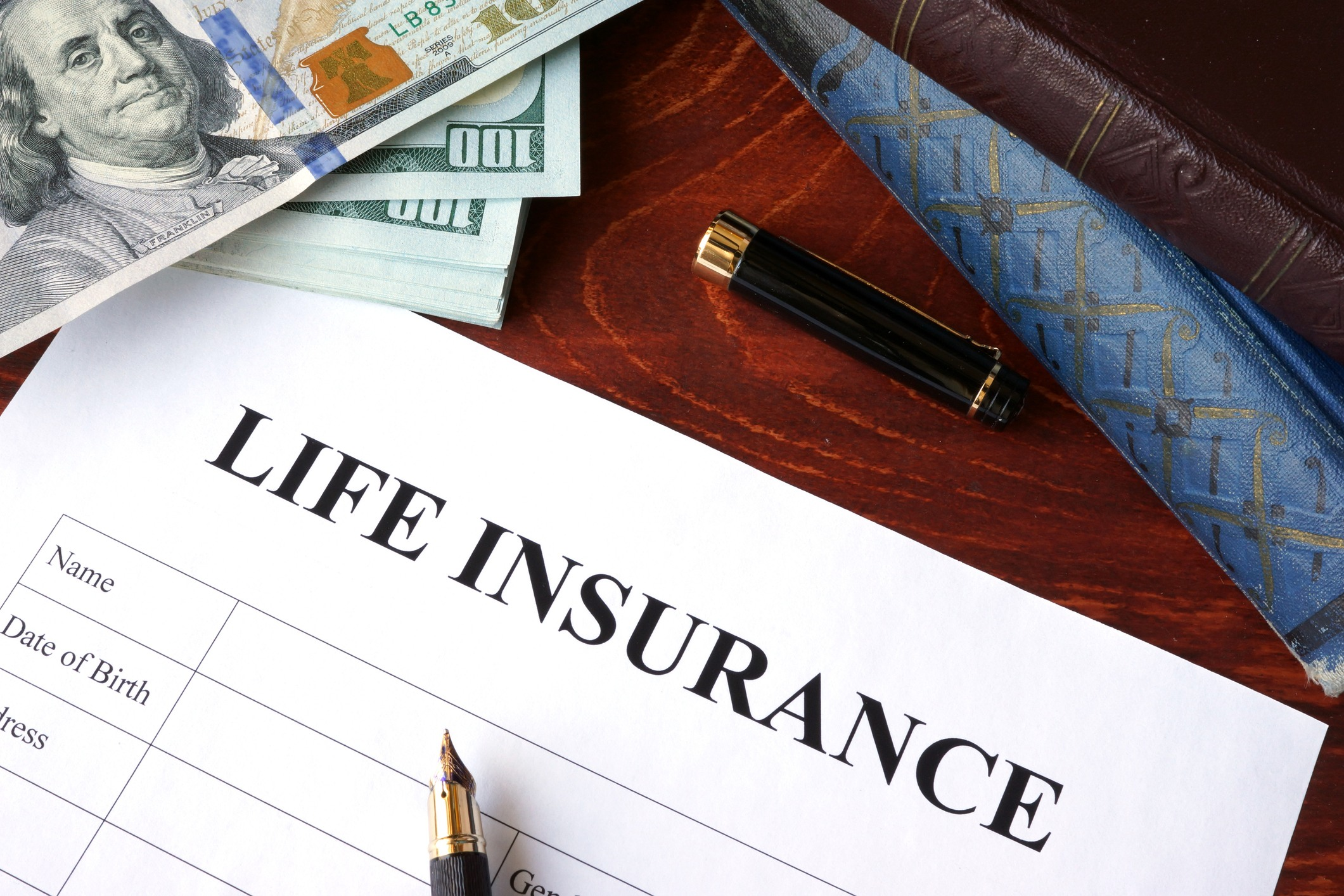Life insurance policy and currency on a table.