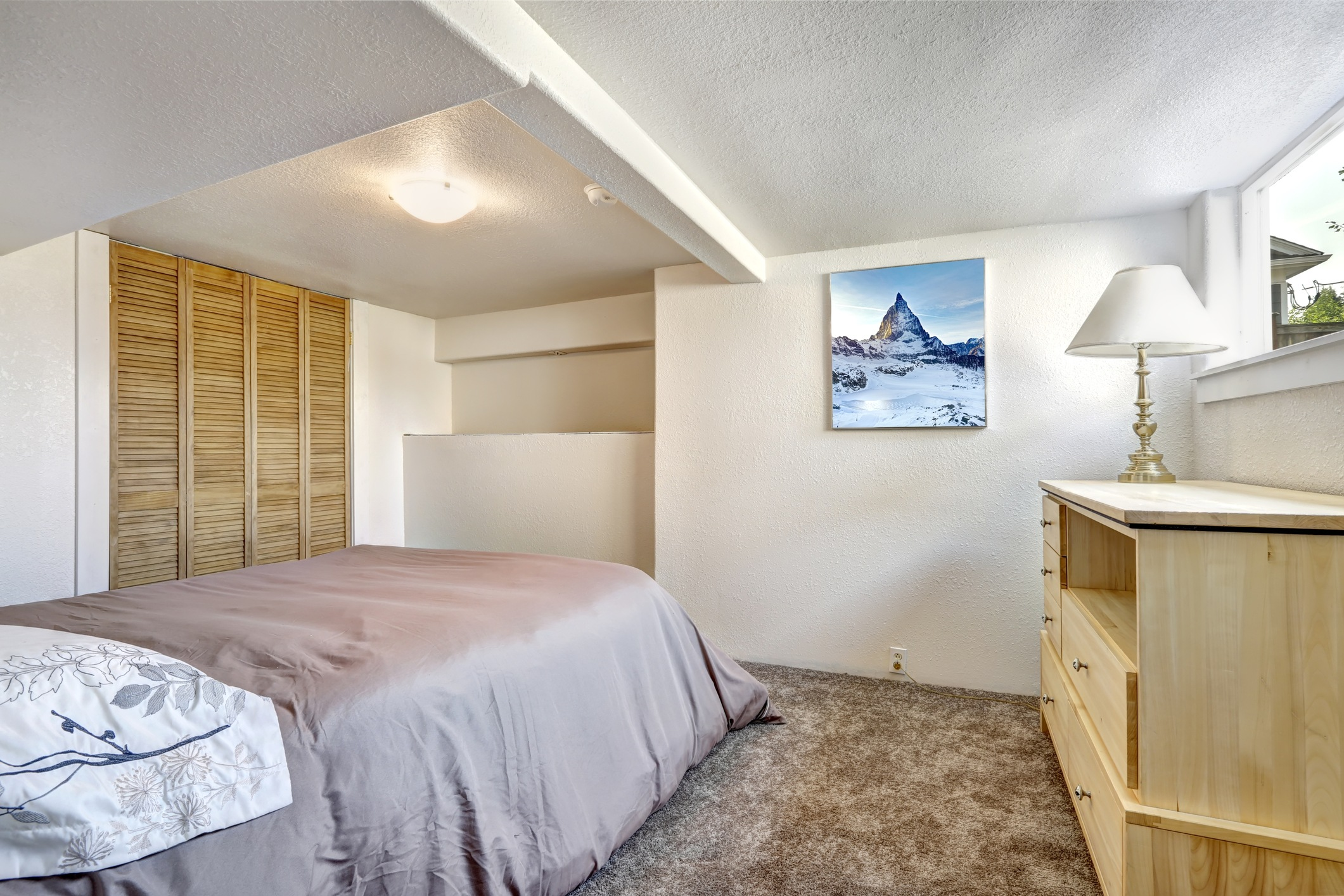 Bedroom with low ceilings and carper