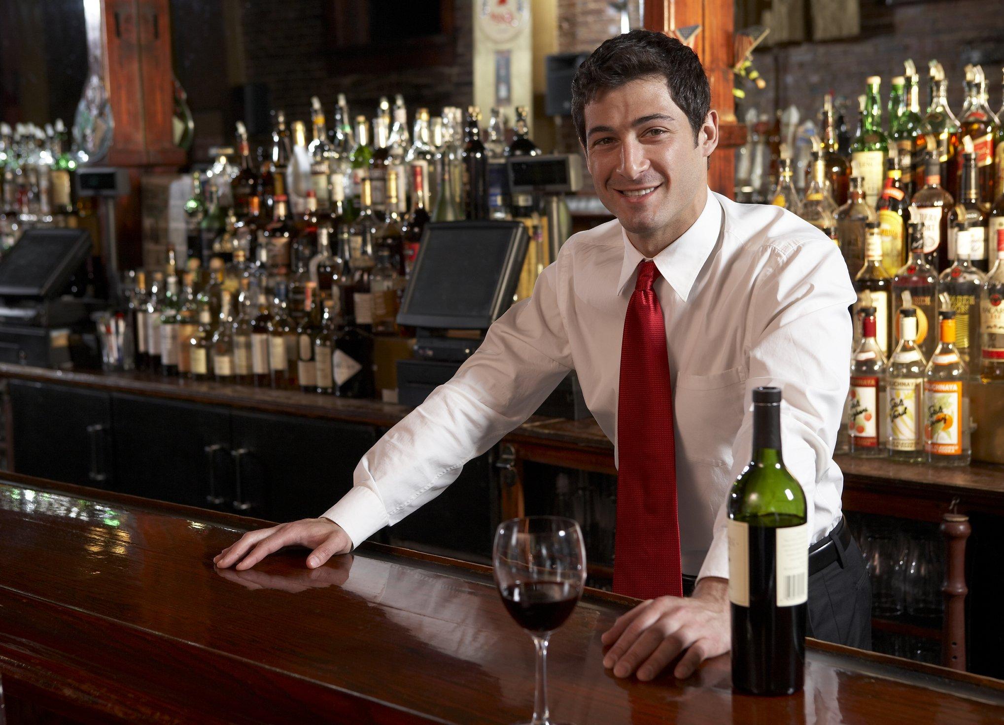 Bartender behind bar counter in pub, portrait