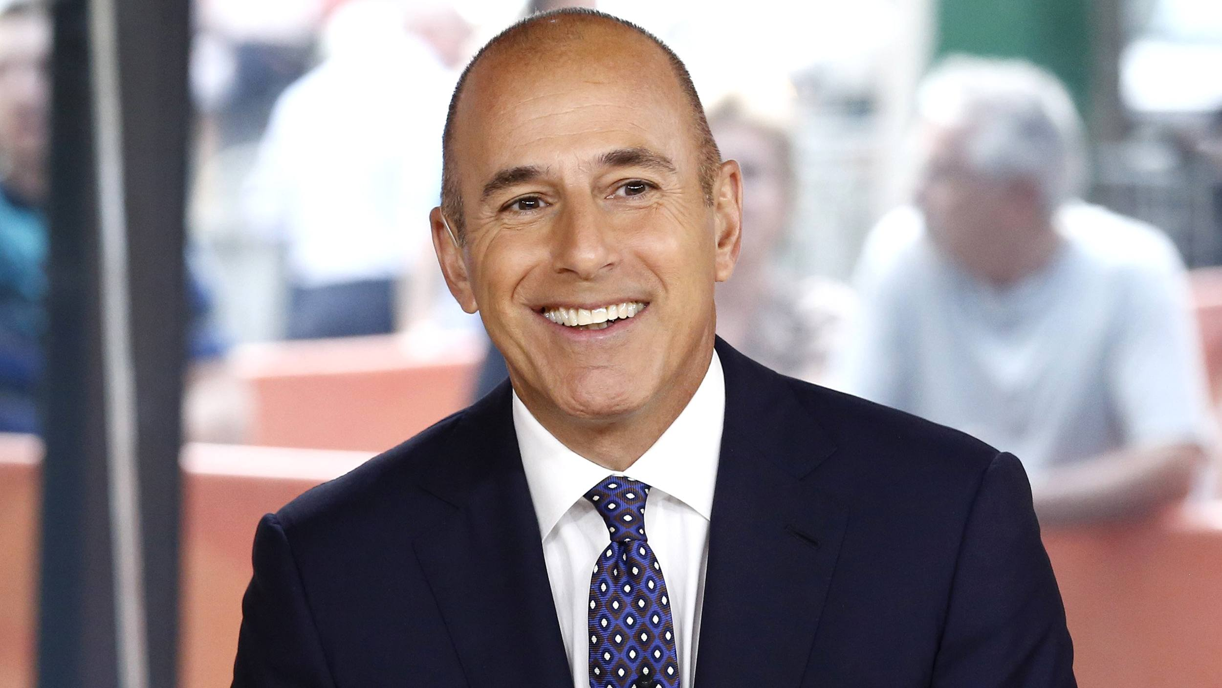 matt lauer smiles on set of Today in a dark suit and speckled tie