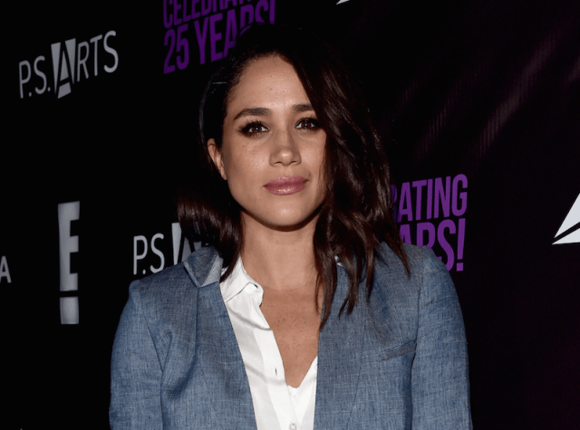 Meghan Markle poses in a gray suit jacket.