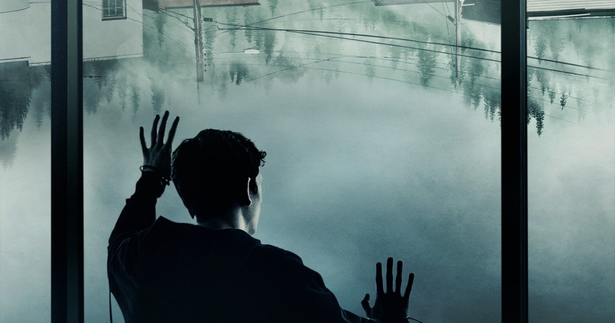 The silhouette of a man keeps his hands against a misted window