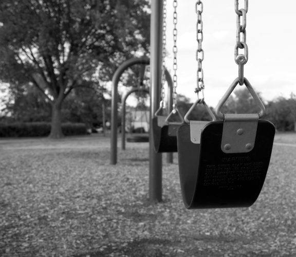 Empty park swings seen at a playground.