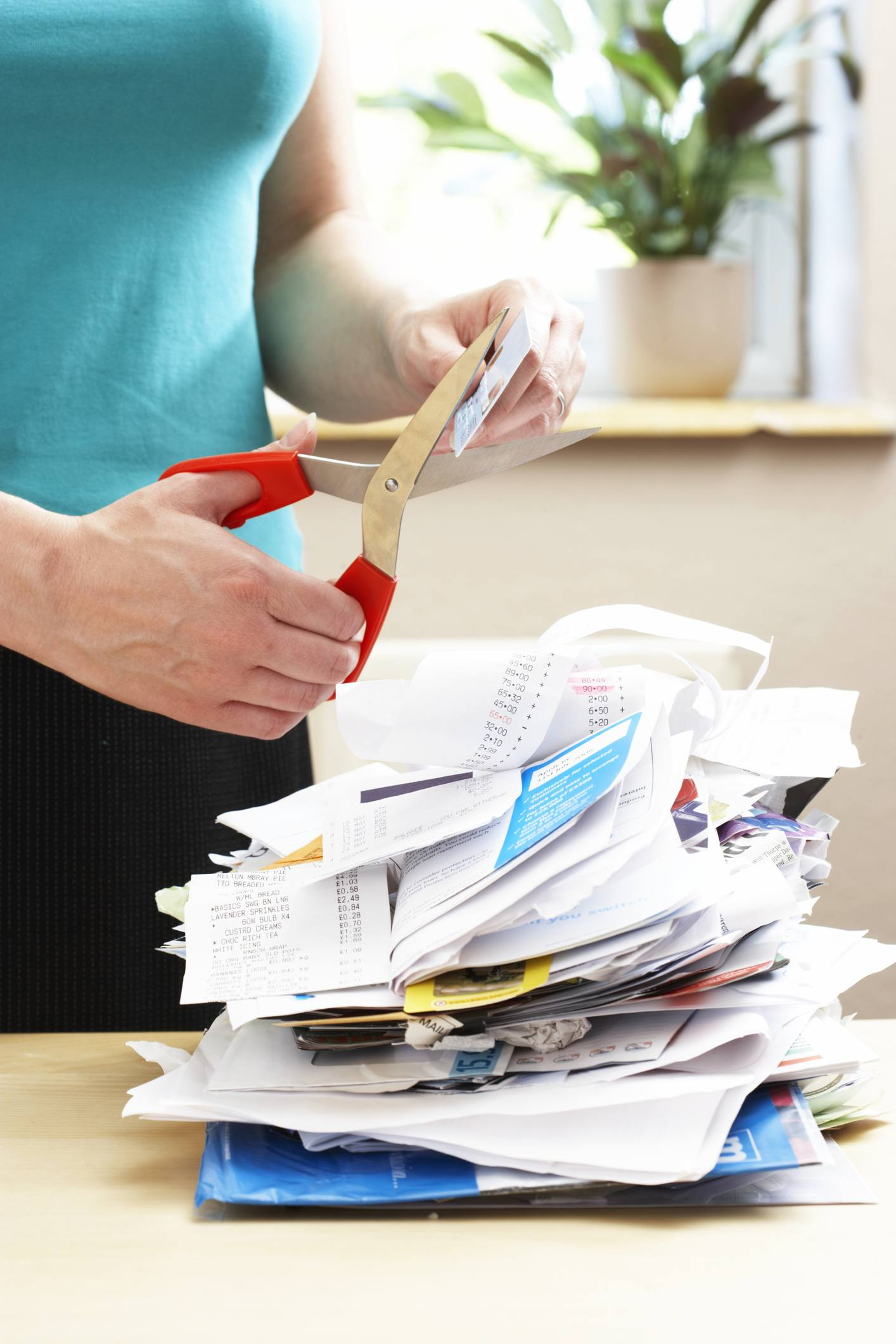 Woman cutting credit card over piled receipts and bills, close-up