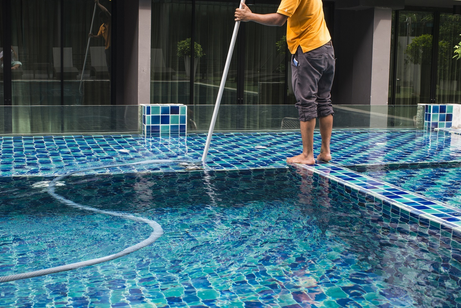 Man cleans a pool