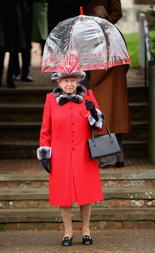 Queen Elizabeth outside holding an umbrella