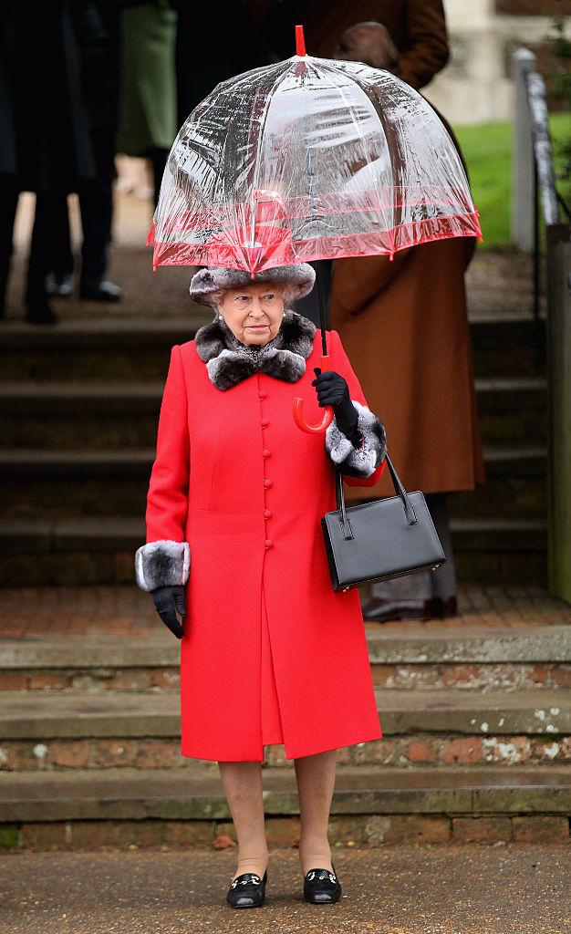 Queen Elizabeth outside holding an umbrella