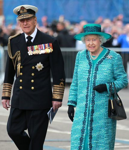 Queen Elizabeth II and Prince Phillip walking together in front of a public crowd.