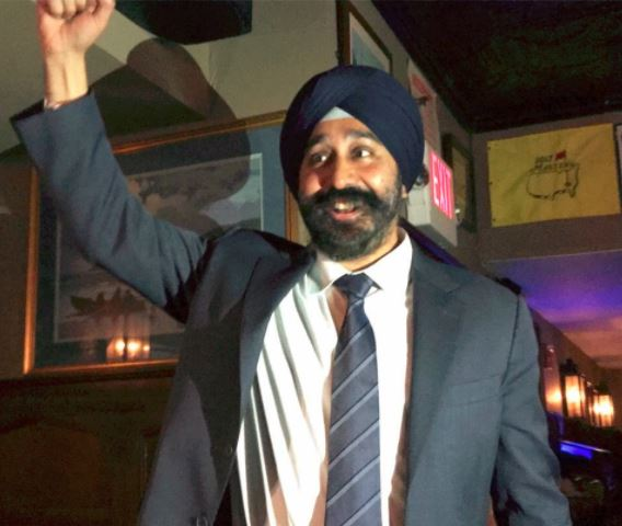 ravinder bhalla in a suit and tie and white shirt waves to the crowd