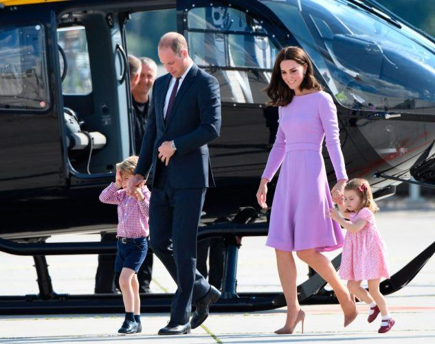 Prince William and Kate Middleton walking by a helicopter