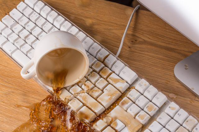 Cup of tea or coffee spilling over a keyboard