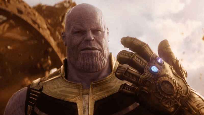 Thanos holds up an Infinity Gauntlet with two Infinity Stones
