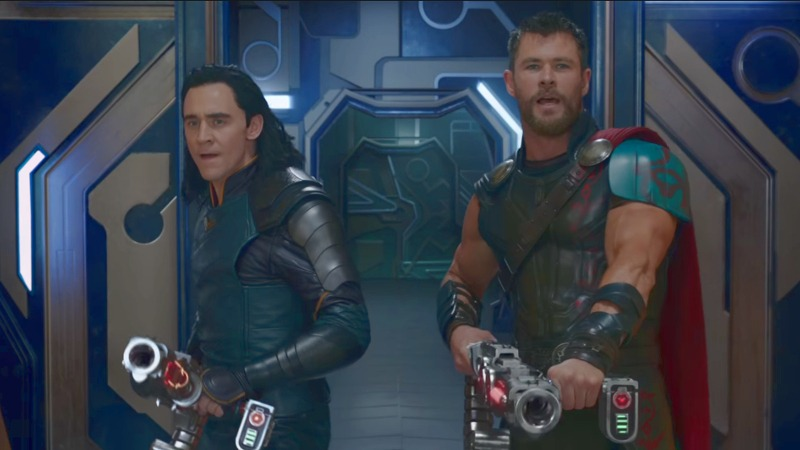 Thor and Loki hold up weapons