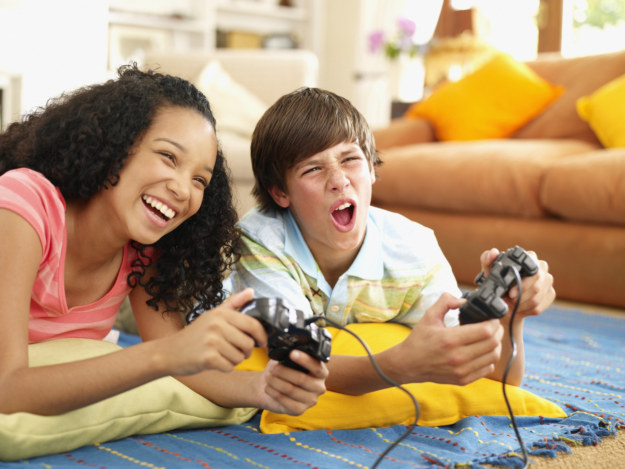 Teenage girl and boy playing video games