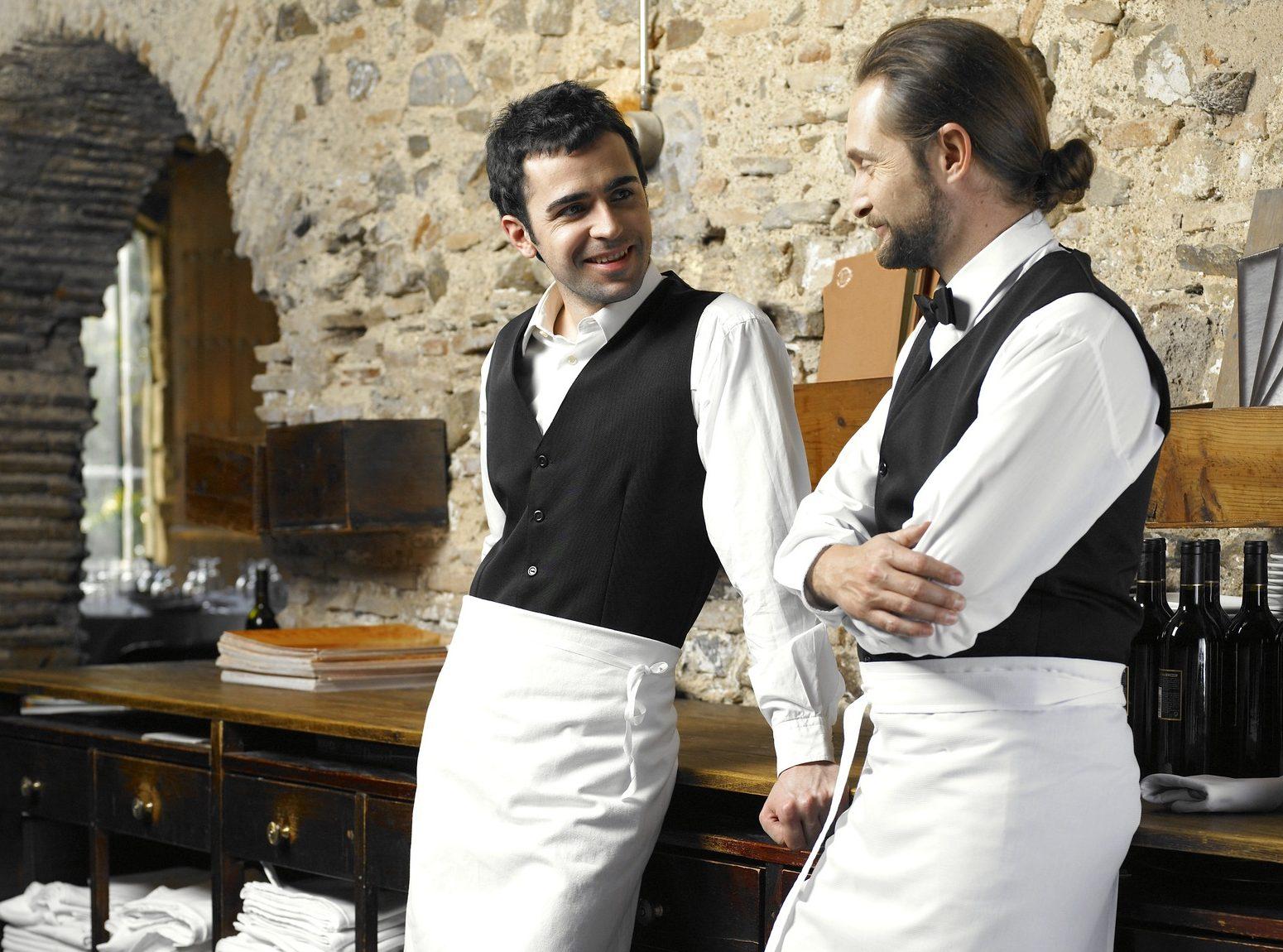 Two waiters talking in restaurant
