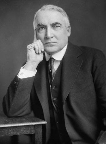 Warren G. Harding posing on top of a desk while wearing a three piece suit.
