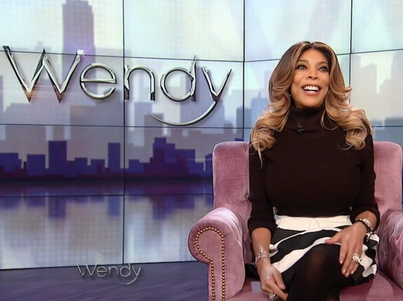 Wendy Williams sits in a pink armchair on the set of her show