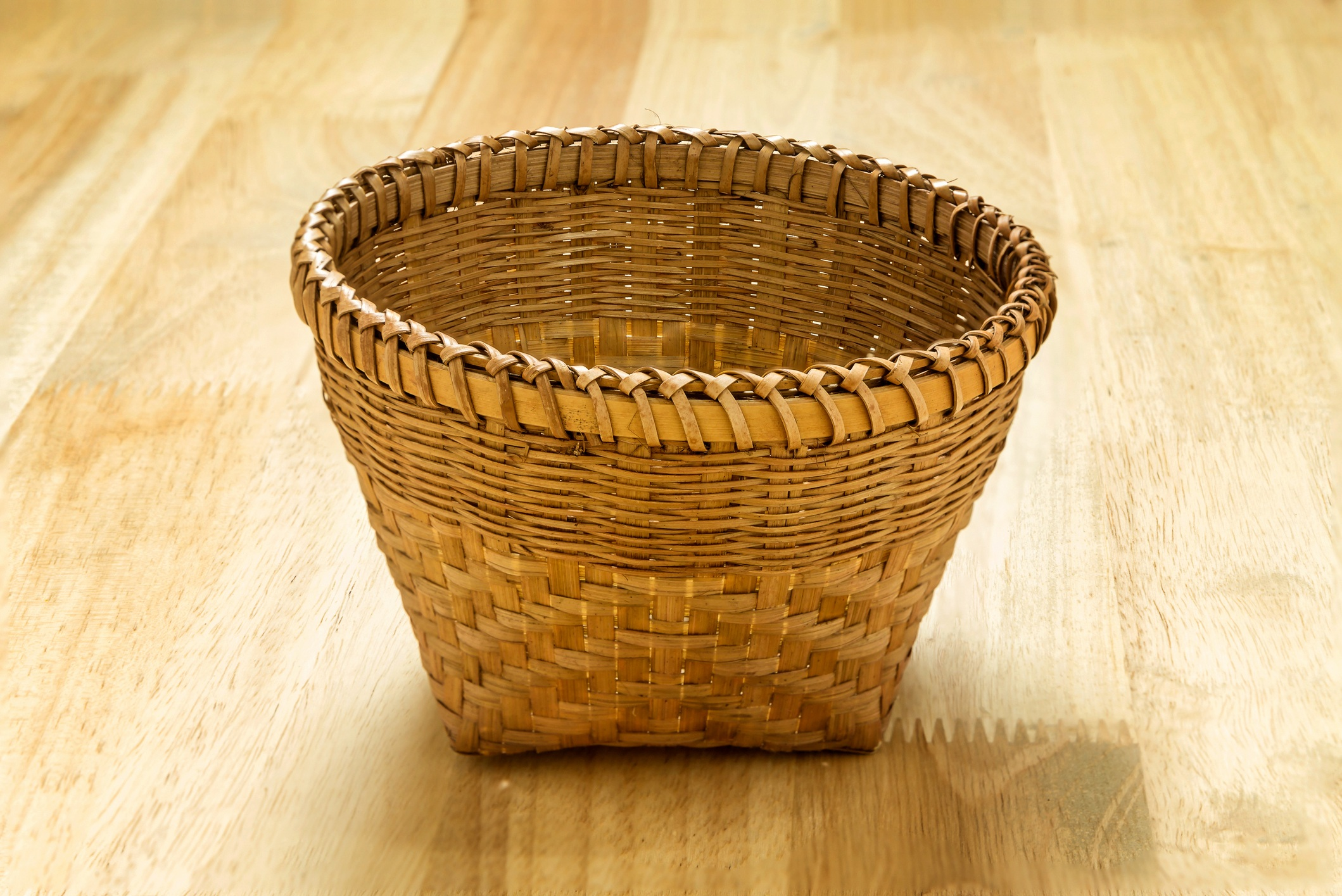 Wicker bamboo basket on wooden table