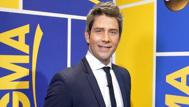 Arie Luyendyk Jr smiles while looking into a camera