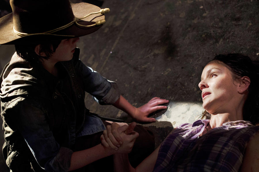 Carl holds the hand of his dying mom