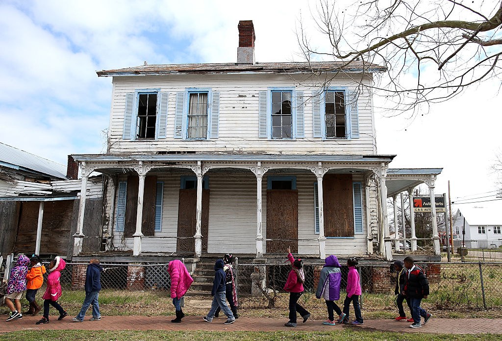 School kids walk by a vacant home that is along the historic route that civil rights marchers took during the Selma to Montgomery march