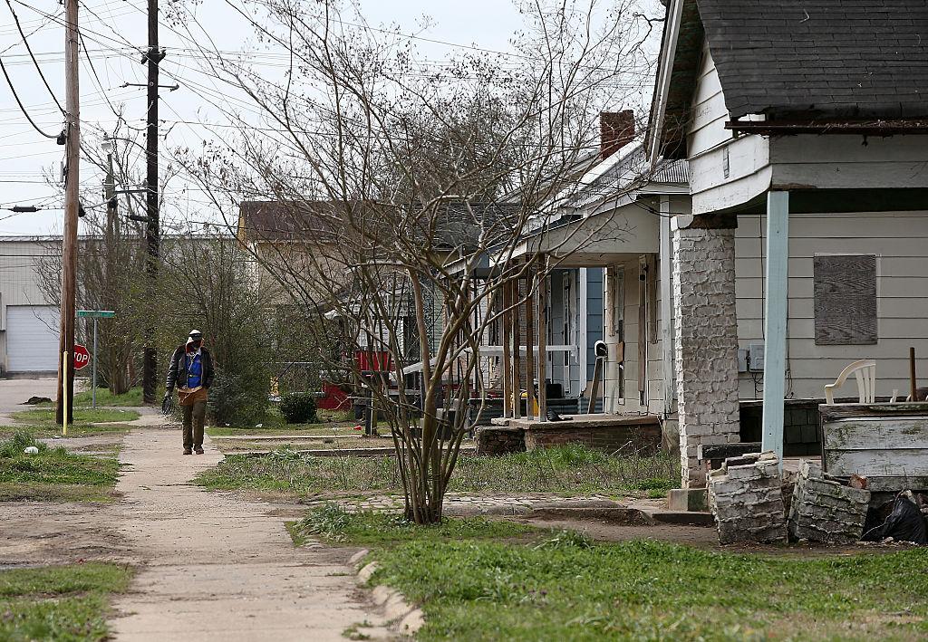 A pedestrian walks through a neighborhood with run down homes
