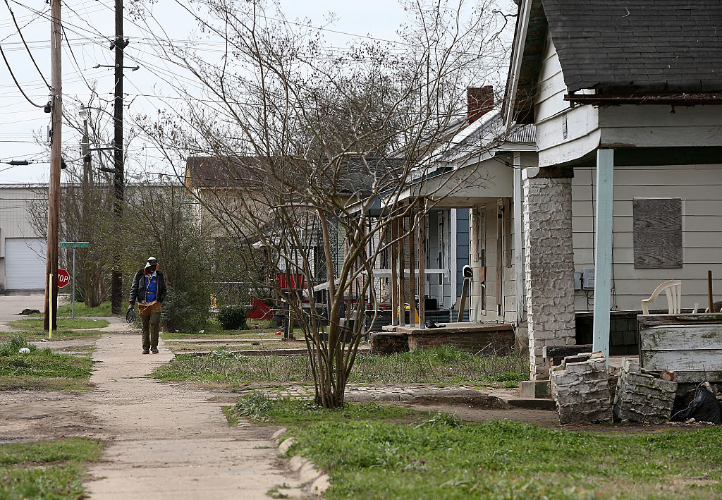 A pedestrian walks through a neighborhood with run down homes