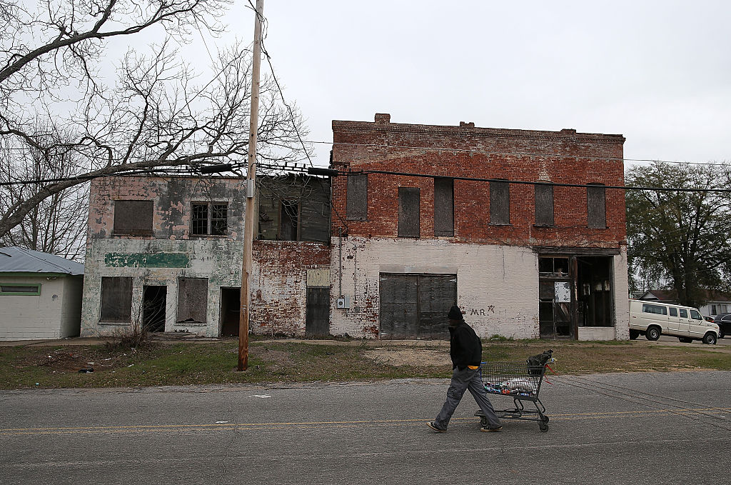 A pedestrian pulls a shopping cart by vacant buildings in Selma, Alabama.