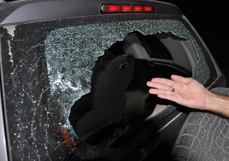 A man shows a smashed bullet found inside the car